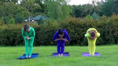 Yoga in the Park. Three Girls in Sport Wear Making Warrior Pose. Stock Footage