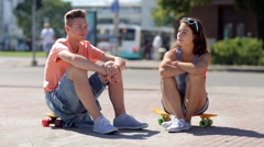 Teenage couple with penny boards talking in city Stock Footage