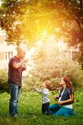 Full-body of happy family in city park at the sunset Stock Photos