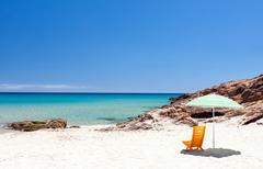 Lounge chair with sun umbrella on a beach Stock Photos
