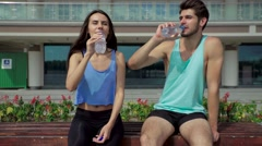 Young sporty couple drinking water, resting after morning training on bench at Stock Footage