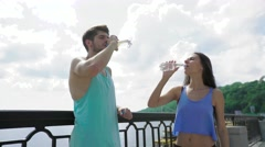 Friendship and lifestyle concept - smiling sporty couple having a break with Stock Footage
