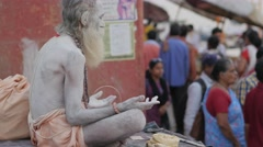 Sadhu smeared with ash meditating on ghats,Varanasi,India Stock Footage