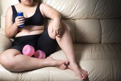 Woman sitting on sofa feeling lazy workout exercise Stock Photos