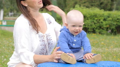 Beautiful baby boy with his mother sitting on a blue rock and smiling in the Stock Footage
