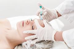 Young woman receiving injections - stock photo