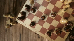 Pretty girl knocks figure in the game of chess. View from above Stock Footage