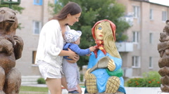Baby boy walking in the park with mom's support near a wooden sculpture of a Stock Footage