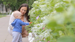 Baby boy walking in the park with mom's support near flowers - stock footage