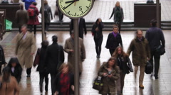 Commuters walking past clocks, Canary Wharf, London, UK Stock Footage