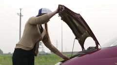 The woman opens the hood of a car Stock Footage