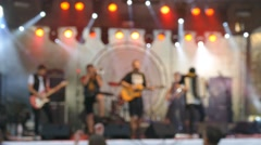 Defocused musicians on stage in front of a crowd of spectators at music concert - stock footage