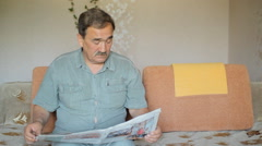 Senior man at home reading newspaper and sitting on sofa Arkistovideo