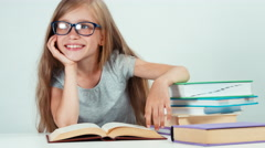 Portrait cute student girl with long blond hair 7-8 years in glasses reading Stock Footage
