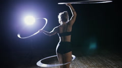 Professional female acrobatic performer rotate hula hoop on stage - stock footage