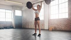 Fit female athlete doing heavy weight lifting Stock Photos