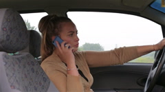 Young beautiful girl talking use your smartphone while sitting behind the wheel Stock Footage
