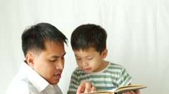 Father and son sitting on bench in the room reading and talking. Stock Footage