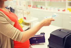 Pregnant woman with money at cashbox in drugstore Stock Photos