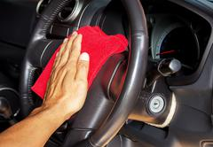 Hand with microfiber cleaning a car steering wheel Kuvituskuvat