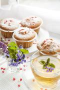 Cup of green tea with lemon balm and tasty muffins with sugar hearts - stock photo
