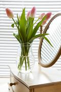 Beautiful bouquet of pink tulips and mirror on backlight background Stock Photos