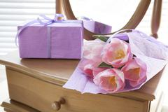 Pink tulips in violet paper, gift and mirror, backlight background Stock Photos