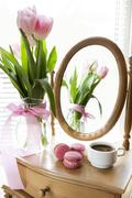 Three pink macaroons and cup of coffee, pink tulips and mirror, backlight bac Stock Photos