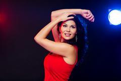 beautiful sexy woman in red dancing at nightclub - stock photo