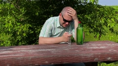 Man thinking near bottle of alcohol on table Stock Footage