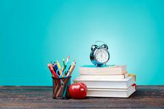 Back to School concept. Books, colored pencils and clock Stock Photos