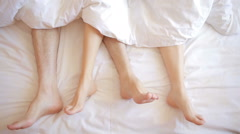 A man and a woman in bed. male and female legs top view, white linens Stock Footage