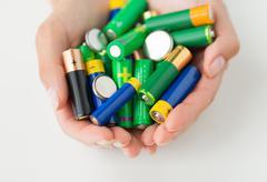 Close up of hands holding alkaline batteries heap Stock Photos