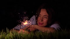 Romantic thoughtful girl laying on the grass with burning sparkler at night Stock Footage