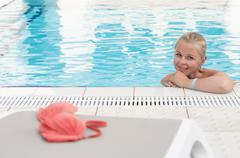 A blonde young woman in a swimming pool with red bikini left by the pool Stock Photos