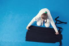 An aikidoka girl folding hakama for Aikido training - stock photo