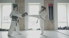 Slow motion Two Taekwondo Girls Train For A Kick On Boxing Paw Stock Footage