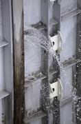 Water spraying through a leaky watergate Stock Photos