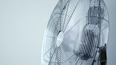 Stylish metallic office fan / ventilator running against white background (loop) Stock Footage