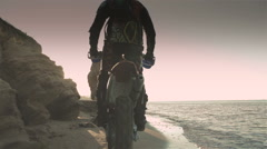 Off-road motorbike rides on a sandy beach in the early morning Stock Footage