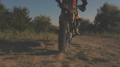 Off-road motorbike goes on the road in a field Stock Footage