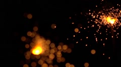 Two orange sparklers against dark background. Super slow motion shallow focus Stock Footage