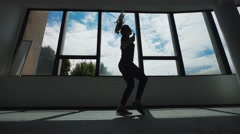 Silhouette of young caucasian woman jogger workout with jumping rope, side view Stock Footage