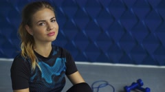 Close up portrait of charming young blonde smiling on camera in the gym - stock footage