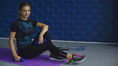Side view of cute blonde trainer posing on fitness mat with dumbbells in modern Stock Footage
