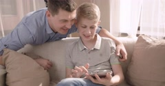 Young handsome man greets her teen son sitting on sofa with tablet. Slow motion Stock Footage