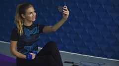 Young beautiful sporty woman making selfie photo sitting on mat with dumbbell on Stock Footage