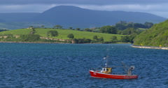 Red Fishing Trawler, green hills, deep blue water . Slow Motion. 2K Stock Footage