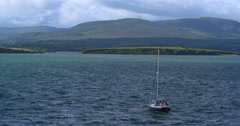 Sailing boat in Bantry Bay, Ireland with green mountains. Slow Motion. 2K Stock Footage