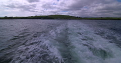 Boat departs green island. Outboard motor wash and waves. 2K Slow Motion Stock Footage